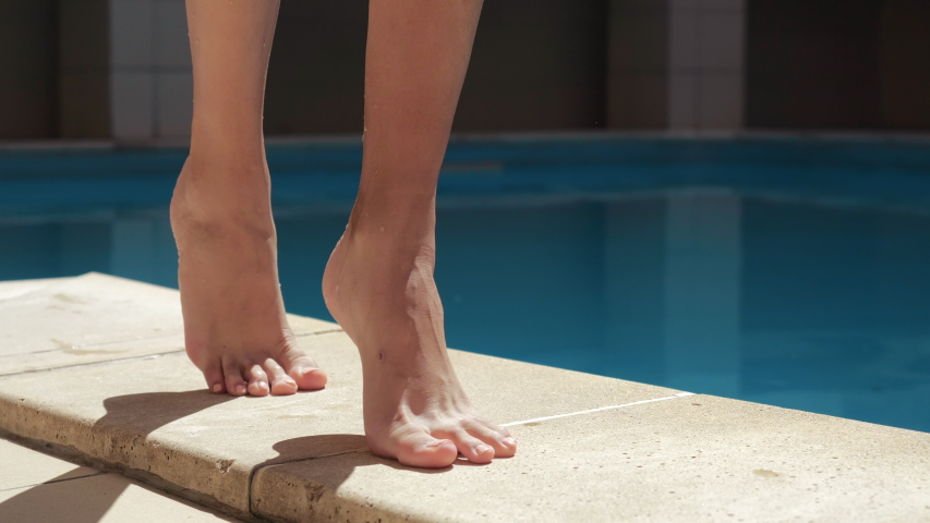 Close up view of slim female tanning barefoot legs careful walking on poolside in spa resort. Woman stepping near pool water tough ground by wet toes, summer relaxation and joy in spa abroad | Shutterstock HD Video #1056932099