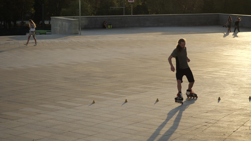 Young long-haired man roller skater is dancing between cones in a nice evening in a city park. Freestyle slalom Roller skating between cones in slow motion. | Shutterstock HD Video #1056932126