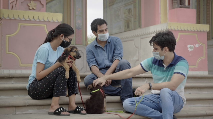 Three friends wearing protective face mask with two cute pet dogs spending time or socialising together outdoors. A group of young male and female hanging out amid Corona virus/ COVID 19 epidemic