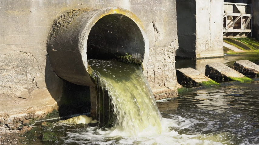 Dirty water flows from the pipe into the river, environmental pollution. Sewerage, treatment facilities