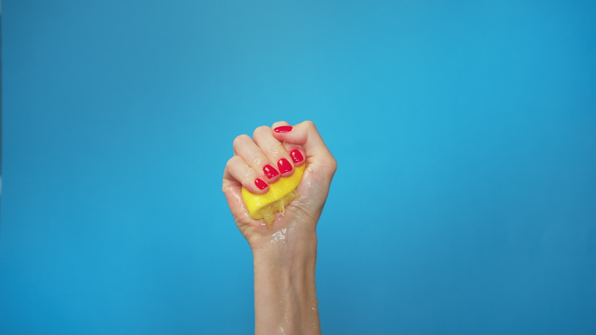 Slow Motion squeeze juice from lemon, close up woman hand squeezes half yellow lemon on blue background. Exhausted.