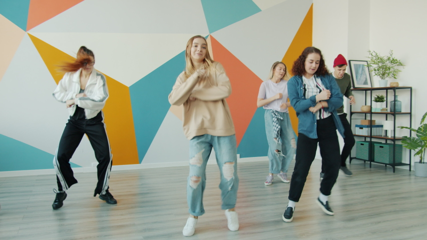 Active young people are dancing in modern hip-hop class moving arms and legs having fun together. Hobby, youth and contemporary art concept. | Shutterstock HD Video #1056942674