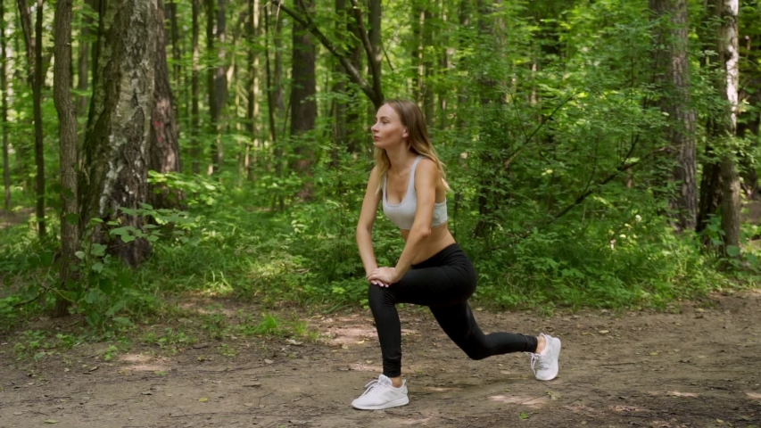 Young woman warms up before a fitness workout in the Park. A healthy young woman is warming up in the open air. | Shutterstock HD Video #1056943400