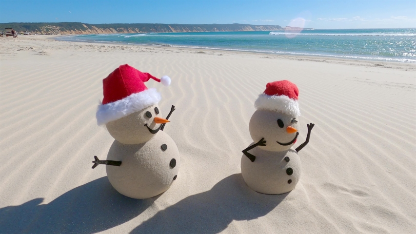 Two Sandy Christmas Snowmen are celebrating Christmas on a beautiful beach, zoom out | Shutterstock HD Video #1056954617
