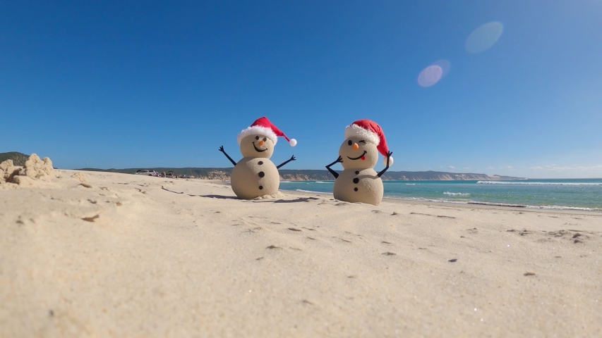Two Sandy Christmas Snowmen are celebrating Christmas on a beautiful beach, zoom out | Shutterstock HD Video #1056954620