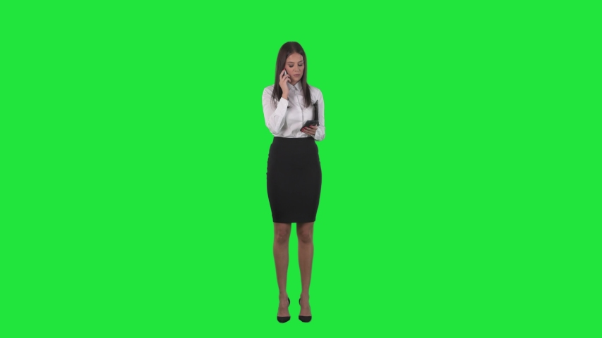 Young pretty busy business woman having two phone call using tablet computer. Full length on green screen background