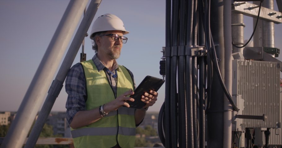 Medium shot of an engineer using a tablet while working on 5g antenna Royalty-Free Stock Footage #1056961412