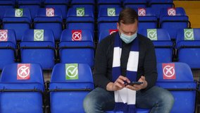 4K: One football fan in the stadium on his phone with Social Distancing Ticks or crosses for Coronavirus COVID-19. Face Mask. Stock Video Clip Footage
