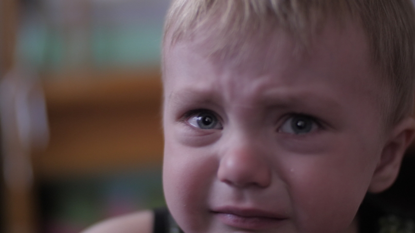 Lovely cute little boy is sad and crying sitting on the bed in the room, slow motion | Shutterstock HD Video #1056962102