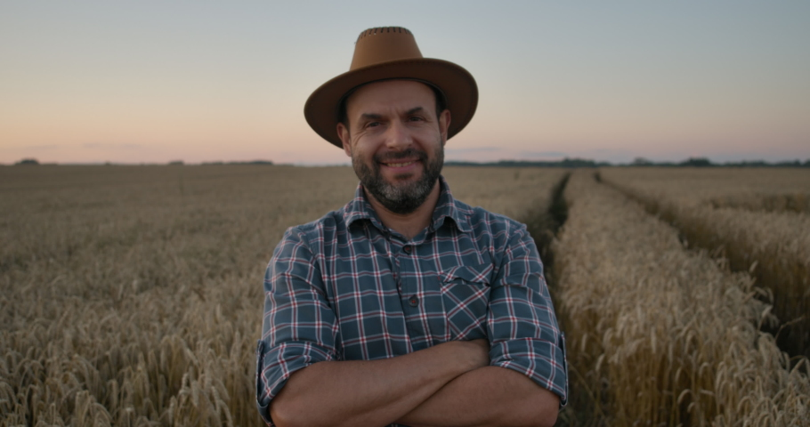 Portrait Caucasian Farmer Man in Plaid Shirt in Hat and Looking in Field. Farmland Sunset Landscape Agriculture. Portrait Farmer Bearded Man With Hat Standing in Wheat Field. Farm Worker. Sunset Sky.