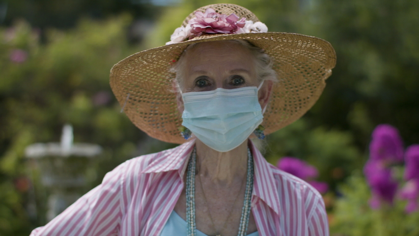 Senior citizen gardening while wearing a protective face mask due to global pandemic. Gardening and enjoying retirement with social distancing and safety. Shot in 4k.  | Shutterstock HD Video #1056974225