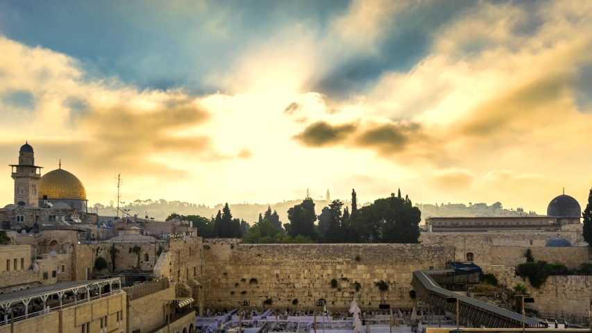 Beautiful time lapse of sunrise clouds moving fast over the Temple Mount: Dome of the Rock, Western Wall and Al Aqsa Mosque; with Jewish people praying in sections because of covid-19 regulations  Royalty-Free Stock Footage #1056974954