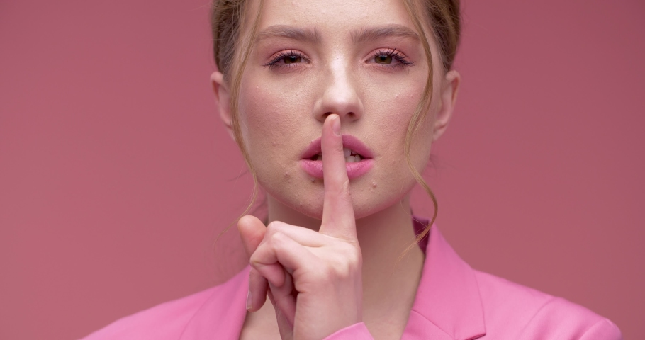 Pretty young redheaded girl making Gesture of shhh, Secret, Silence. Beautiful woman showing sign hush holding finger near lips. Sympathetic girl making Hush Gesture by the Forefinger. Playfully Girl.   Shutterstock HD Video #1056976130