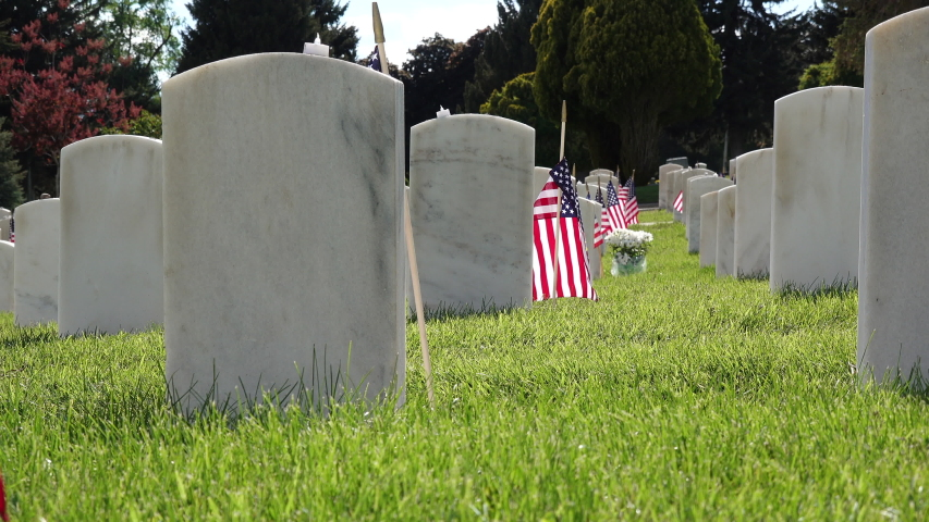 Man puts yellow flowers next to military headstone decorated with American flag for Memorial Day