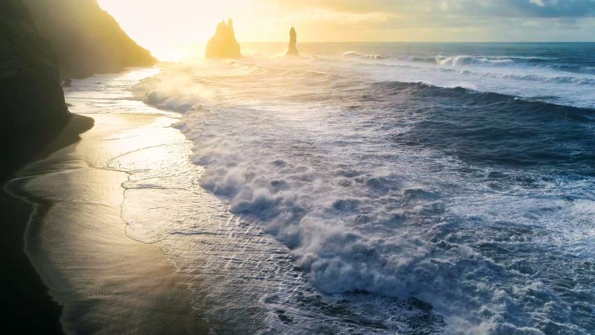 Huge waves crashing and splashing on a Black Beach in Iceland. Aerial view of Atlantic ocean on sunrise Royalty-Free Stock Footage #1056977759