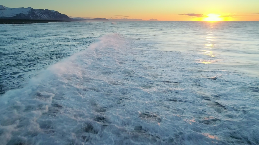 Flying over the Ocean during golden hour. Giant waves foaming and splashing in the ocean Royalty-Free Stock Footage #1056977762