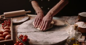 Senior professional italian restaurant chef working, shaping floured dough for pizza. Experienced cooker making pizza using traditional recipe, isolated on black background close up 4k footage