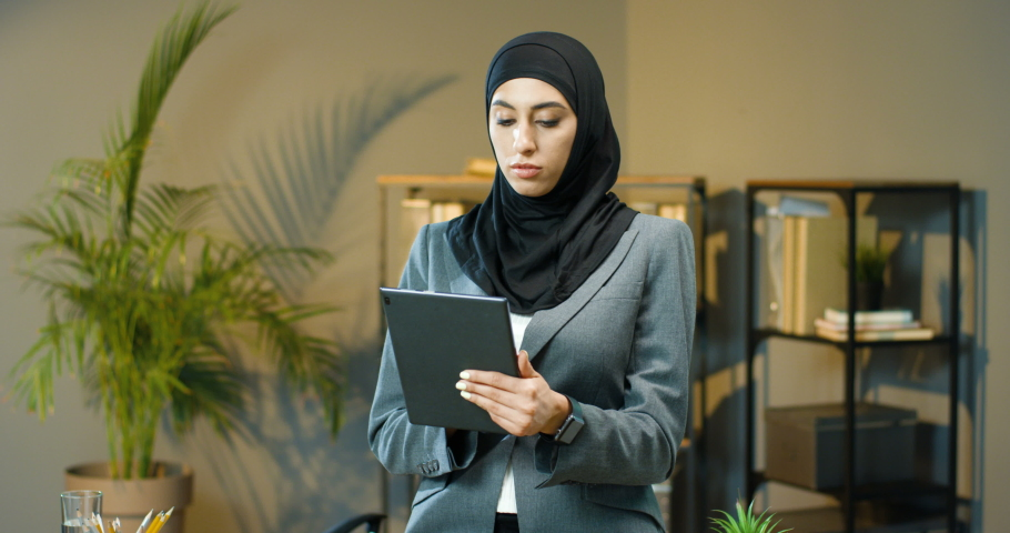 Portrait Arabic beautiful woman in black hijab standing in office, tapping and scrolling on tablet device screen. Muslim happy businesswoman in headscarf smiling to camera. Arab female using computer