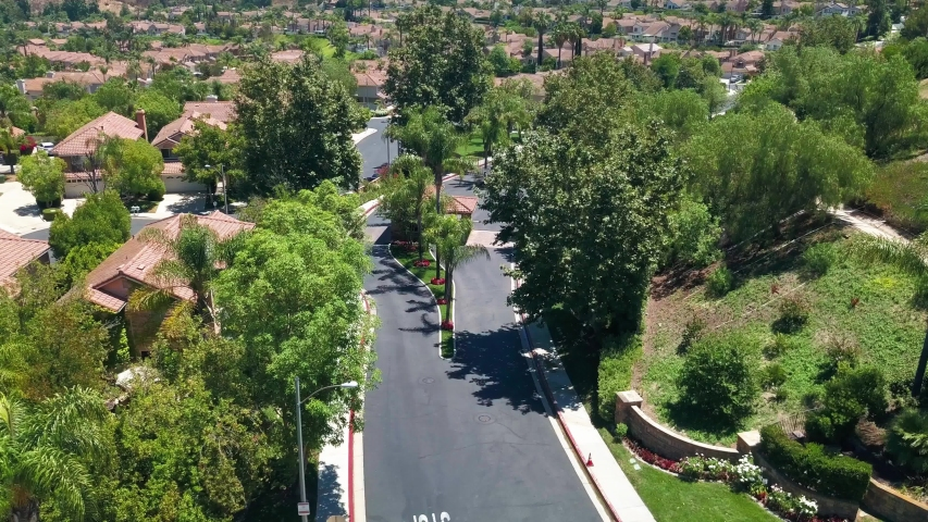 Descending aerial shot of the security gate at the entrance to an upscale suburban community in Southern CA. | Shutterstock HD Video #1056980144