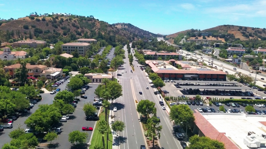 Aerial wide shot over an upscale shopping center next to the highway in Southern California. 4K | Shutterstock HD Video #1056980147