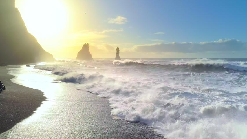 Huge waves crashing and splashing on a Black Beach in Iceland. Aerial view of Atlantic ocean on sunrise Royalty-Free Stock Footage #1056980306
