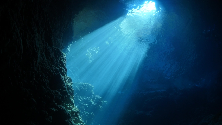 Sun rays sun beams and sun shine underwater in cave beautiful light scenery in ocean scuba divers to see
