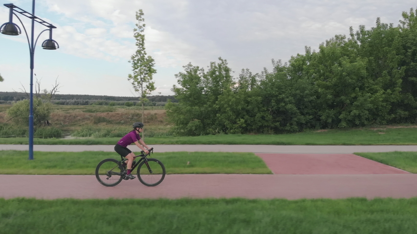 Cyclist girl twists pedals on aero bike on cycle path in summer, drone shot. Woman bike rider rides on bicycle. Female triathlete is pedaling on cycle. Cycling and triathlon concept. Healthy lifestyle