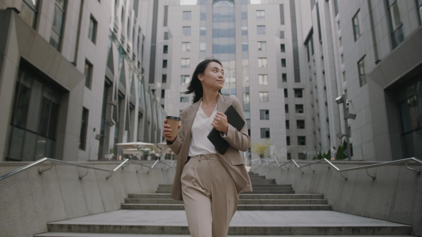 Successful young beautiful asian woman with tablet and coffee cup walking between business buildings and smiling with joy. Attractive business girl. Career people.