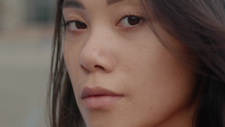 Face of amazing young attractive mixed race woman with black hair looking at camera outdoors. Sensual asian girl portrait on the street. Citizens. People.