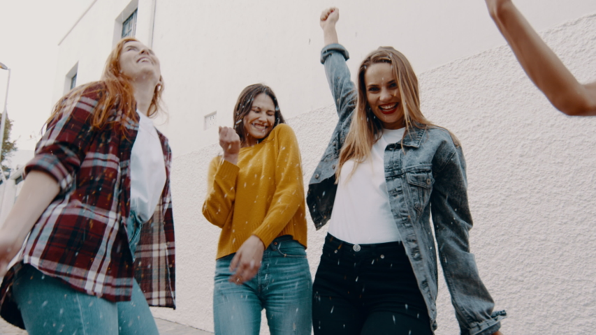 Group of female friends dancing together and blowing confetti. Group of women enjoying dancing outdoors.  Royalty-Free Stock Footage #1056988925