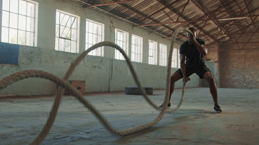 Fitness man exercising with battle rope abandoned warehouse. Tough man working out in cross training gym made inside old factory.