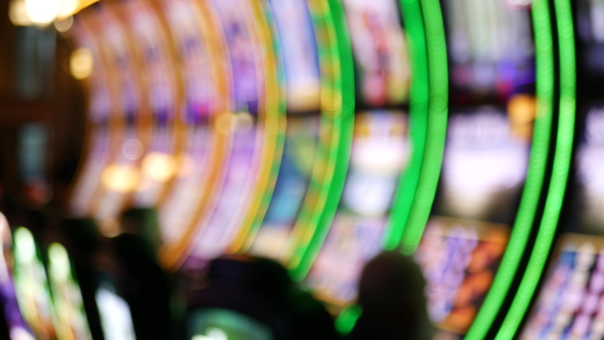 Defocused slot machines glow in casino on fabulous Las Vegas Strip, USA. Blurred gambling jackpot slots in hotel near Fremont street. Illuminated neon fruit machine for risk money playing and betting. | Shutterstock HD Video #1056989570