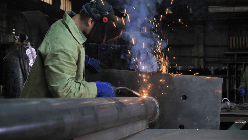 Industrial Process, Heat Electrode Work, Metal Parts Welding with Soldering Iron by Two Men Laborers Team Wearing Safety Uniform at Heavy Manufacturing Factory Indoor. Metalwork Assembly, Construction Royalty-Free Stock Footage #1056997061