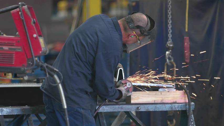 American Worker Uses Angle Grinder To Cut Part while Working in Manufacturing in USA, fiery sparks