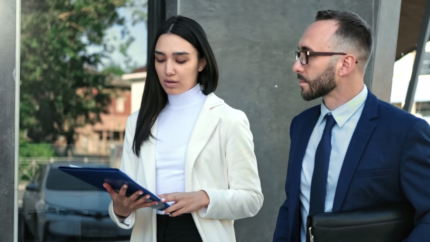 Colleague discuss business hold folder with document walking together at modern office building exterior. Man and woman talk at informal meeting steadicam establish shot. Medium shot on RED camera | Shutterstock HD Video #1057004252