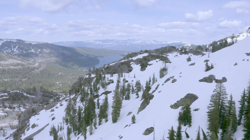 Aerial view above Lake Tahoe, California. Flying above the mountains covered by snow, revealing Tahoe lake. Flying towards the lake in winter. Drone footage track in.