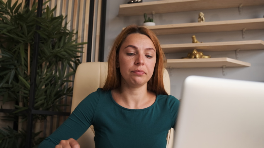 Thoughtful concerned woman working on laptop computer looking away thinking solving problem at home office Royalty-Free Stock Footage #1057005398