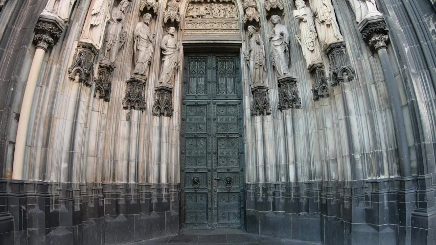 SLOW SHOT Entrance of the Cologne Cathedral (Kolner Dom), Roman Catholic cathedral, located in the city of Cologne, Germany, shows the 19th century decoration. Marble figures of saints on the facade. | Shutterstock HD Video #1057008977