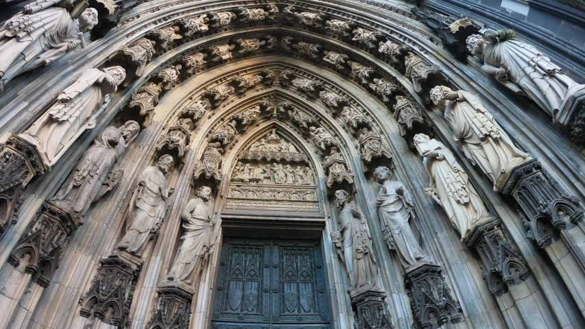 SLOW SHOT Entrance of the Cologne Cathedral (Kolner Dom), Roman Catholic cathedral, located in the city of Cologne, Germany, shows the 19th century decoration. Marble figures of saints on the facade. | Shutterstock HD Video #1057008980
