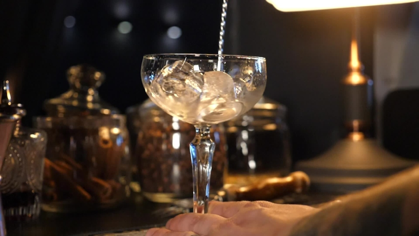Close-up shooting. Bartender is turning the ice in glass using the bar spoon. 4k | Shutterstock HD Video #1057010279