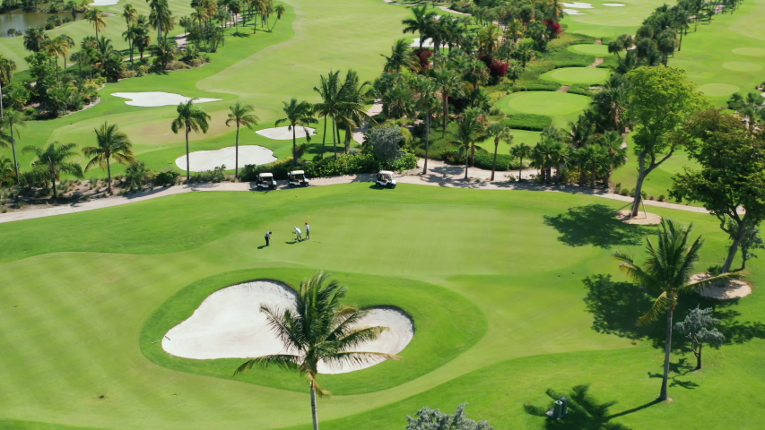 Cinematic overhead view on active men playing the golf game on a sunny summer day. Aerial footage of people on a golf course playing the sport match in Miami, Florida, USA. Background for business