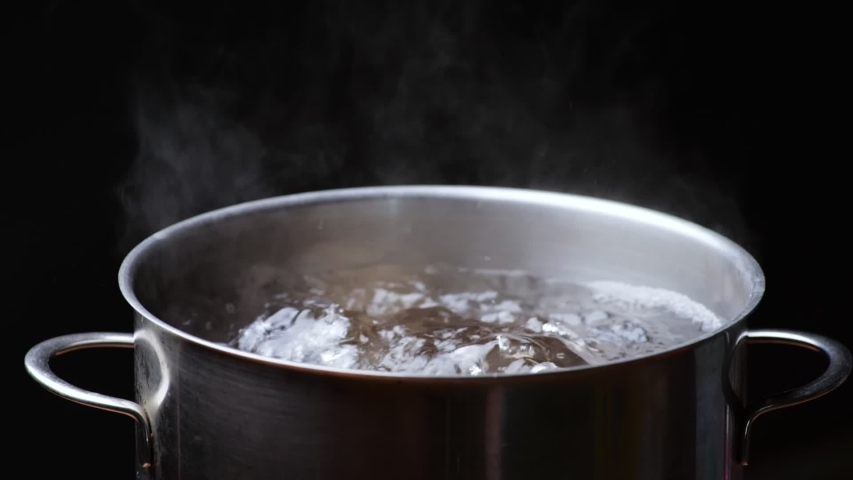 Pot of boiling water over black background. Bubbles of boiling water. Slow motion shot Royalty-Free Stock Footage #1057012280