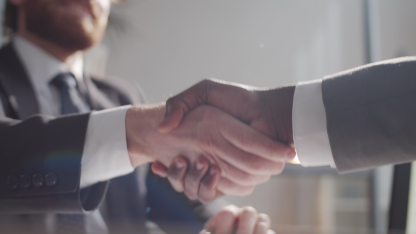 Close up selective focus shot of handshake of two multiethnic business partners in formalwear during meeting in the office. Royalty-Free Stock Footage #1057012790