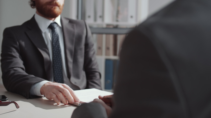 Midsection arc shot of two multiethnic business partners in formalwear shaking hands and having discussion while sitting at table in office Royalty-Free Stock Footage #1057012928