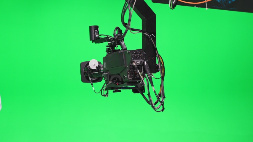 Film crew in green studio shooting video. Chroma - technology of combining two or more images or frames in single composition. Cameraman, director, crew. Filmmaking industry.   Shutterstock HD Video #1057018205