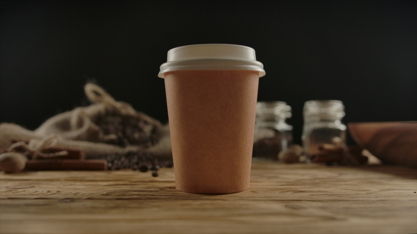 Craft disposable cup for hot drinks presentation. Tea or coffee, espresso, latte, cappuccino for take away. Wood table, coffee traditional beans and spices on the background. Zoom in. Focused on cup Royalty-Free Stock Footage #1057019276
