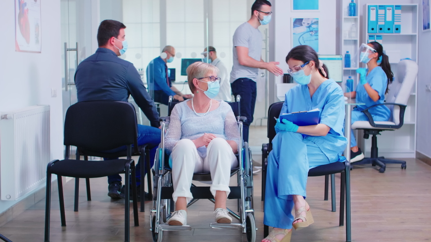 Nurse wearing face mask against coronavirus taking notes on clipboard while talking with disabled senior woman in wheelchair in hospital waiting area. Patients at reception.