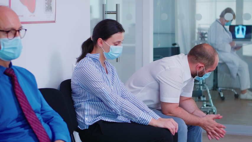 Worried young couple wearing face mask against infection with coronavirus while waiting news from doctor. Wife crying from unfavorable news during covid-19.