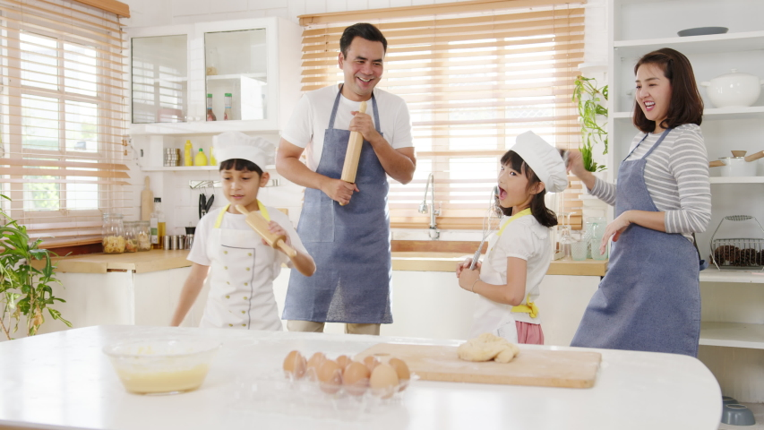 Happy young Asian family with preschool kids have fun listen to music and dancing while cooking baking pastry for breakfast meal in kitchen home in morning. Doing bakery knead dough and bake cookies. Royalty-Free Stock Footage #1057028570