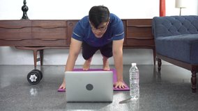 young asian fit man in sportswear doing plank While watching video training fitness  online tutorials on laptop in living room at home . sport male workout in quarantine